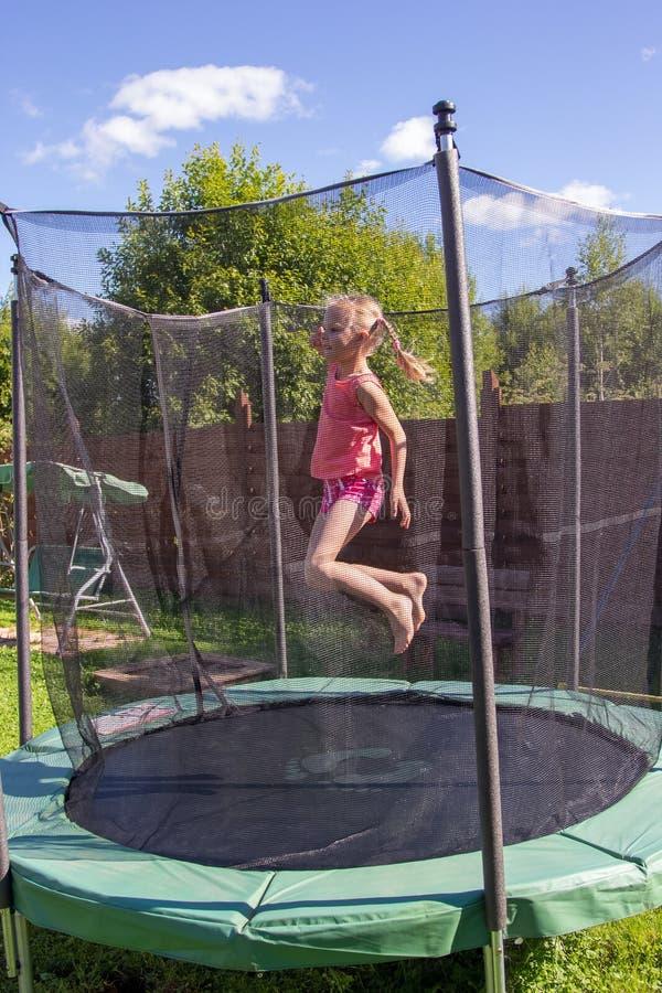 Meisje die op een trampoline achter beschermende netto springen stock fotografie
