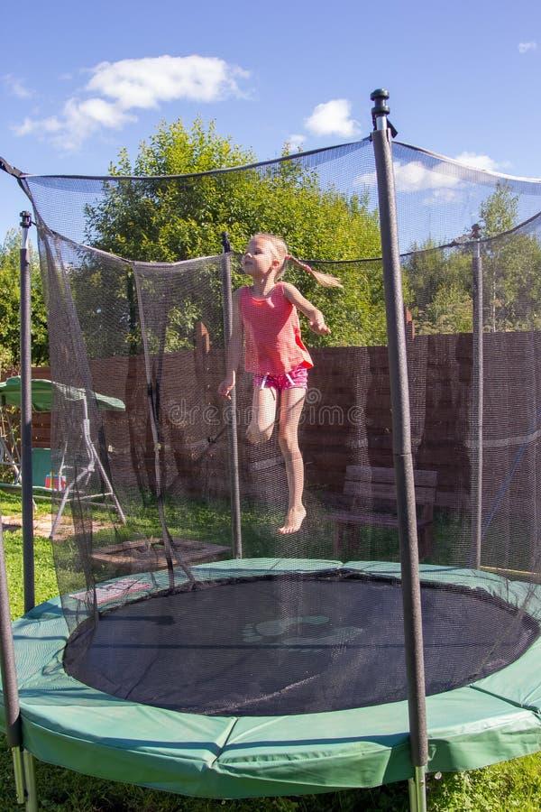 Meisje die op een trampoline achter beschermende netto springen royalty-vrije stock afbeelding