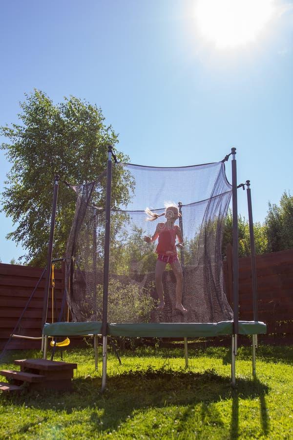 Meisje die op een trampoline achter beschermende netto springen royalty-vrije stock foto's