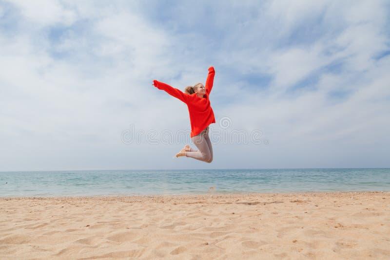 Meisje die op een zandige strand overzeese kust springen stock foto
