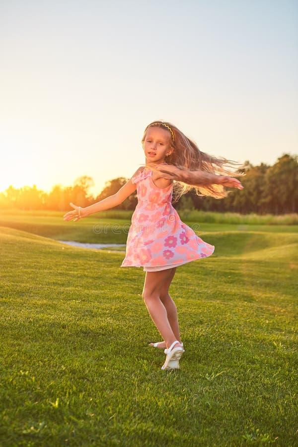 Meisje die op gras dansen stock fotografie
