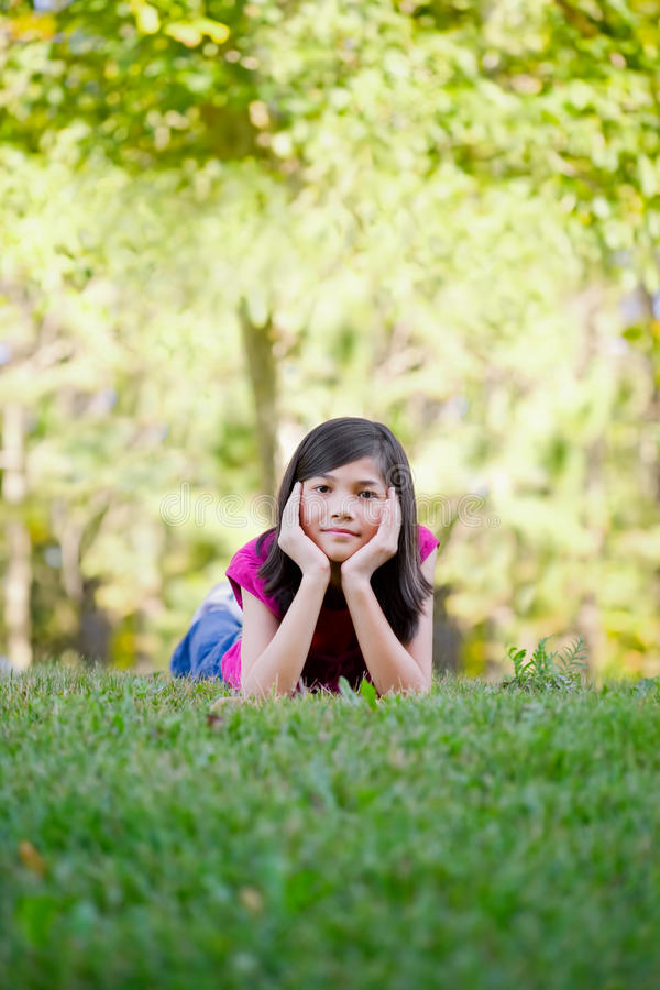 Meisje die op gras liggen stock afbeeldingen