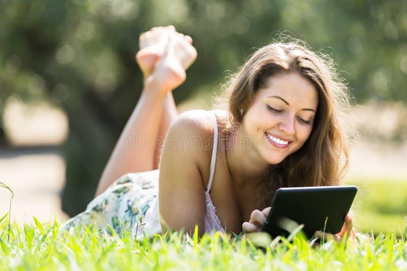 Meisje die op gras met ereader liggen stock fotografie