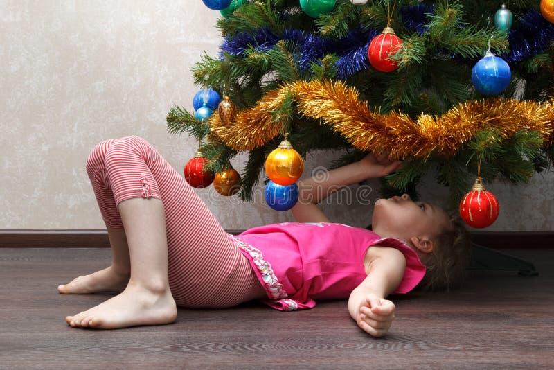 Meisje die op haar terug onder Kerstboom liggen royalty-vrije stock foto's