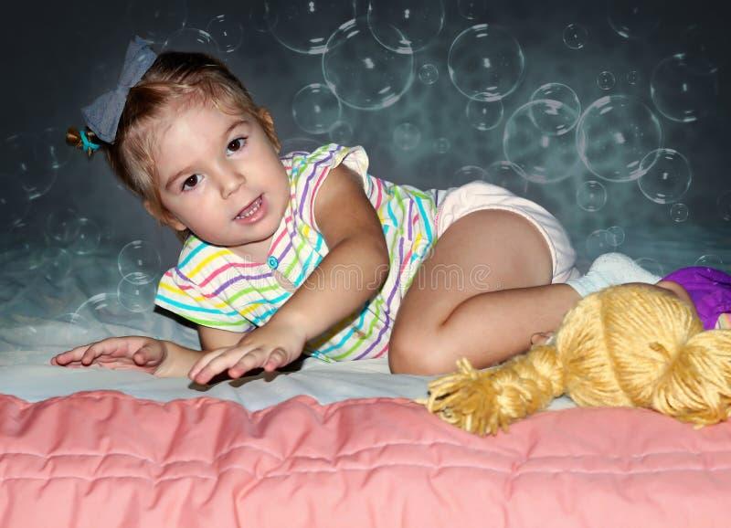 meisje die op het bed kruipen stock foto