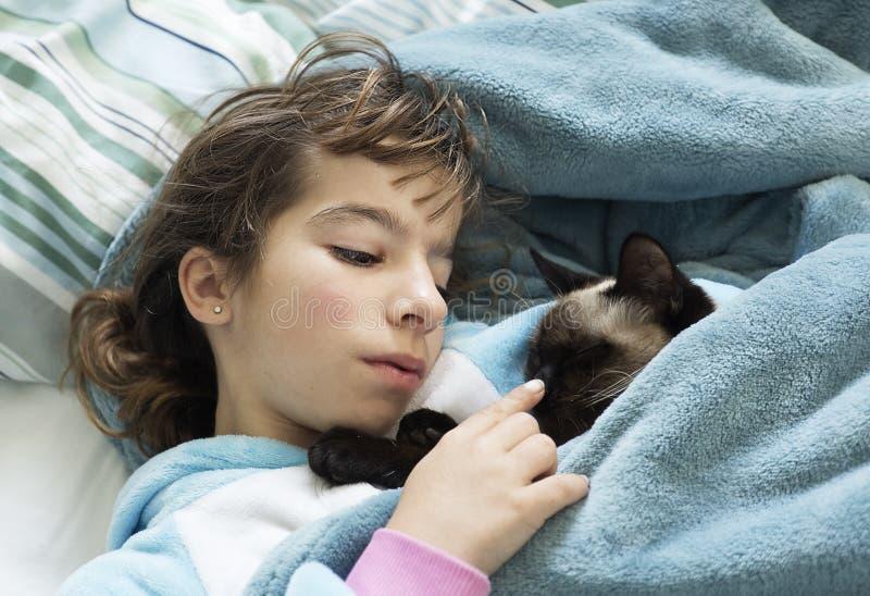 Meisje die op het bed met haar kat liggen stock foto