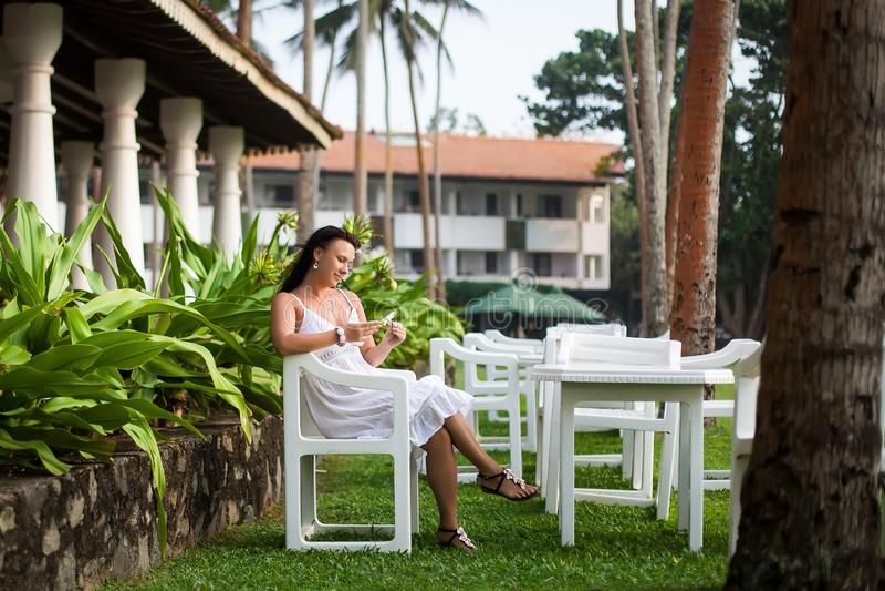 Meisje die op het gazon rusten bruid op wittebroodsweken Hotelgrondgebied Ontspanningsgebied De zitting van de vrouw op een groen royalty-vrije stock fotografie
