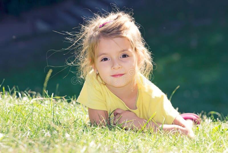 Meisje die op het groene gras liggen Gezicht van de kind het openluchtclose-up royalty-vrije stock foto