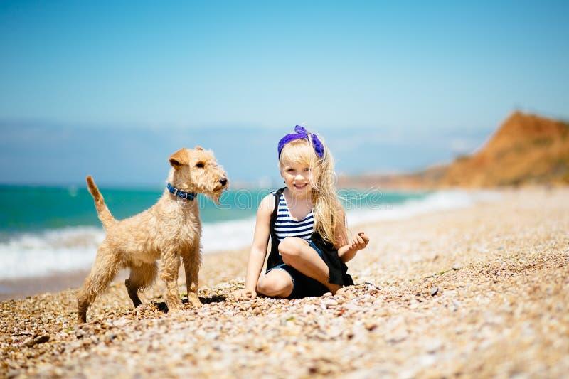 Meisje die op het strand met een puppyterriër lopen royalty-vrije stock foto's