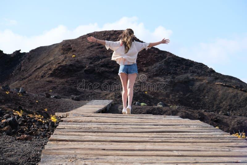 Meisje die op houten weg op vulkanische rots met open wapens lopen stock afbeelding
