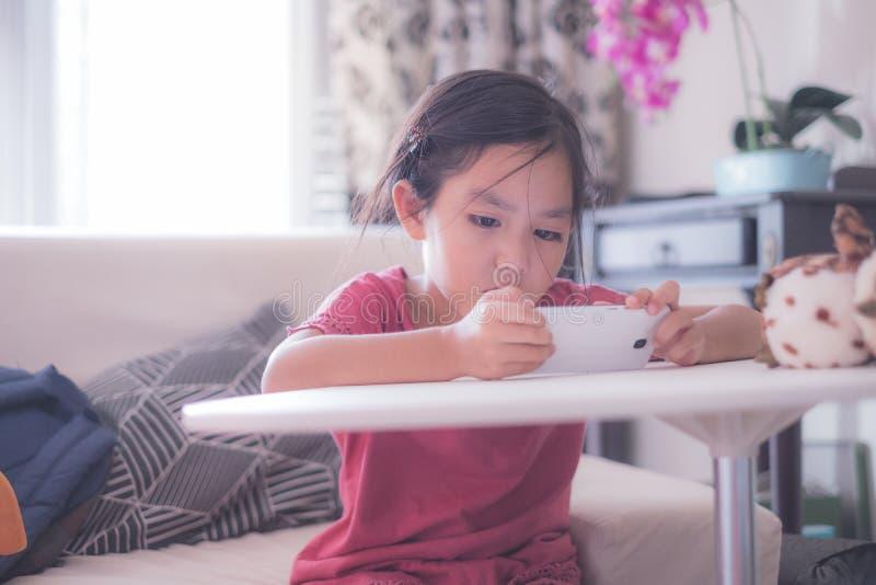 Meisje die op online video op cellphone letten stock foto