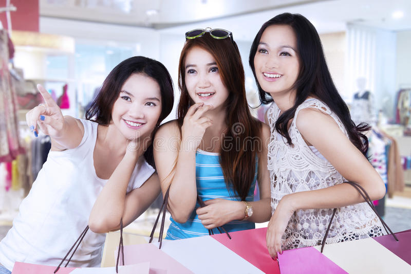 Meisje die op opslag met haar vrienden richten stock foto's