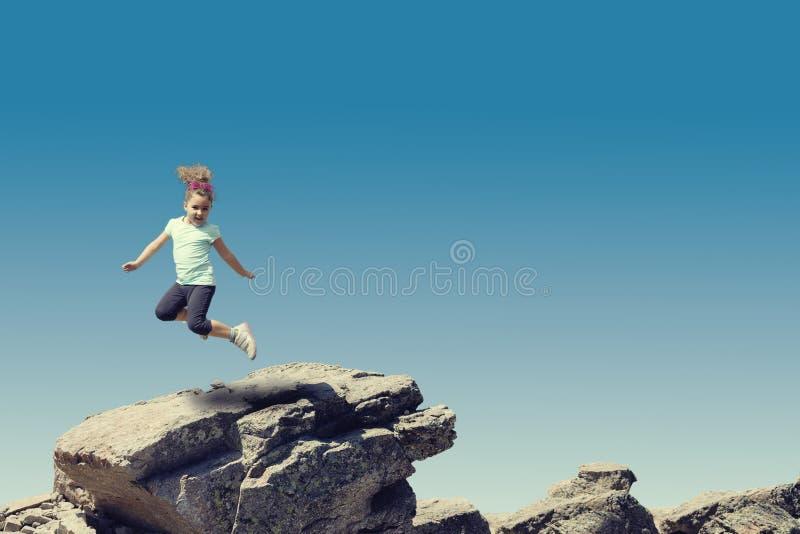 Meisje die op steen springen stock foto