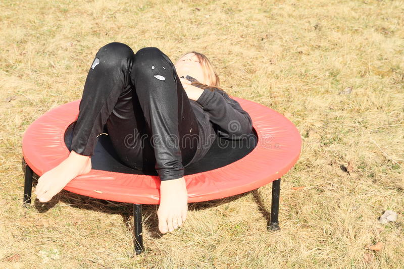 Meisje die op trampoline liggen stock afbeelding