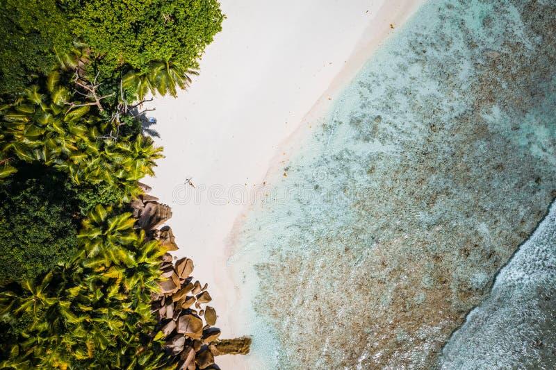 Meisje die op tropisch cocosstrand zonnebaden met mooie rotsen, palmen en oceaangolven Luchthommelschot seychellen royalty-vrije stock afbeeldingen