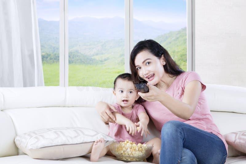 Meisje die op TV met haar moeder letten stock afbeelding