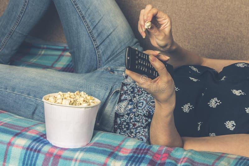 Meisje die op TV met popcorn thuis in de woonkamer letten Het concept luiheid stock afbeeldingen