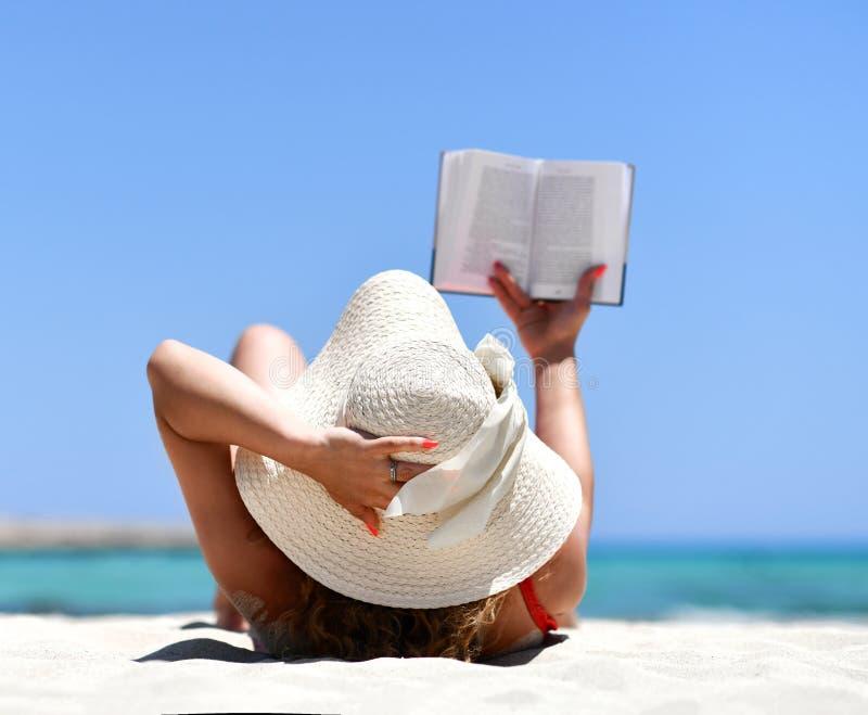 Meisje die op zand overzees kuststrand in wit de lezingsboek van de de zomerhoed liggen stock foto's