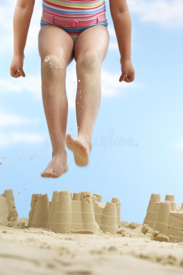 Meisje die op Zandkasteel springen stock afbeelding
