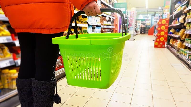 Meisje die in oranje jasje met lege groene het winkelen mand tussen de plank in een opslag lopen stock foto's