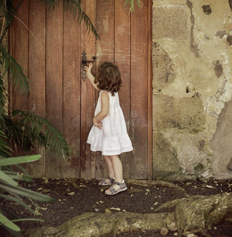 Meisje die oude, houten deur controleren stock afbeelding