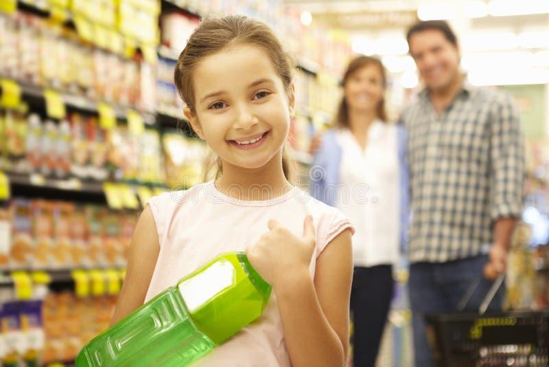 Meisje die ouders met supermarkt het winkelen helpen stock fotografie