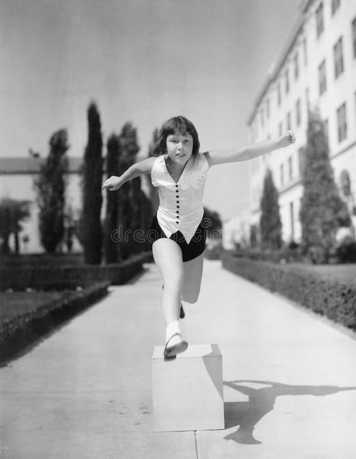 Meisje die over houten blokken springen (Alle afgeschilderde personen leven niet langer en geen landgoed bestaat Leveranciersgara royalty-vrije stock fotografie