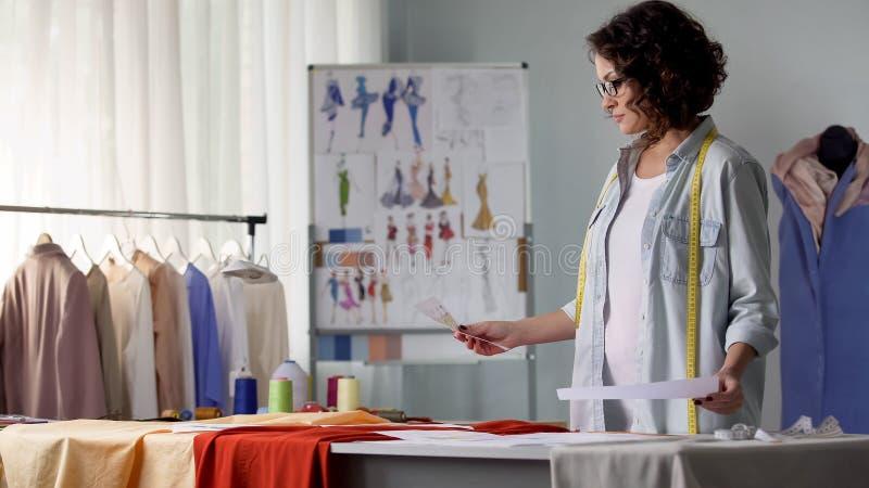 Meisje die overzicht van nieuwe klereninzameling bekijken, jonge ontwerper, creativiteit royalty-vrije stock afbeeldingen