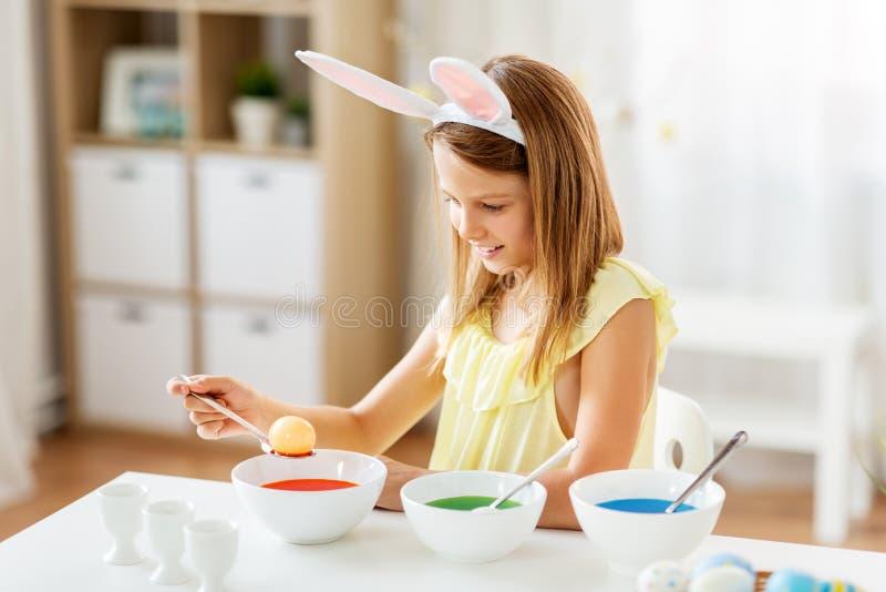 Meisje die paaseieren thuis kleuren door vloeibare kleurstof stock foto's
