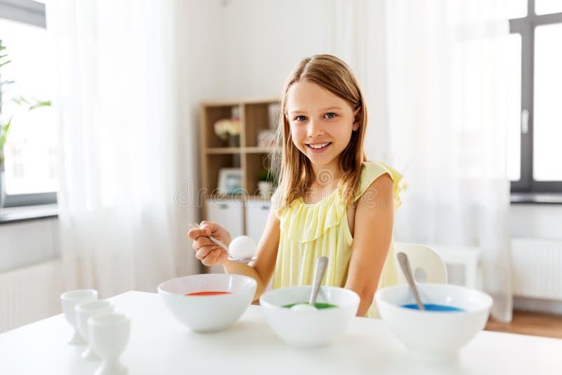 Meisje die paaseieren thuis kleuren door vloeibare kleurstof stock foto