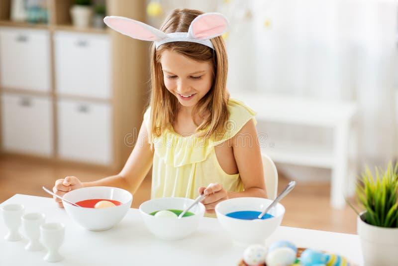 Meisje die paaseieren thuis kleuren door vloeibare kleurstof royalty-vrije stock foto