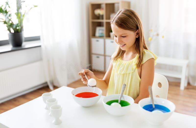 Meisje die paaseieren thuis kleuren door vloeibare kleurstof royalty-vrije stock afbeelding