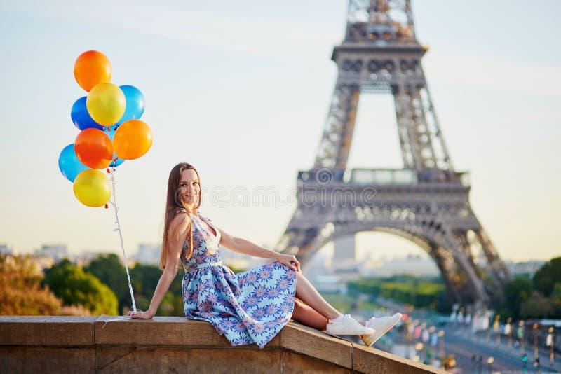 Meisje die in Parijs met bos van ballons de toren van Eiffel bekijken stock afbeeldingen