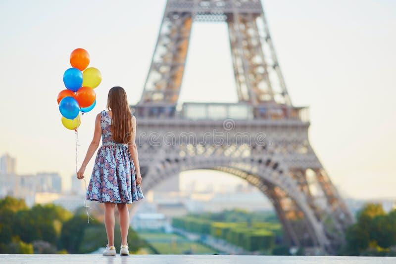 Meisje die in Parijs met bos van ballons de toren van Eiffel bekijken royalty-vrije stock fotografie