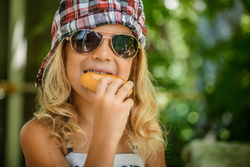 Meisje die in plaid GLB ongezuurd broodje eten stock afbeeldingen