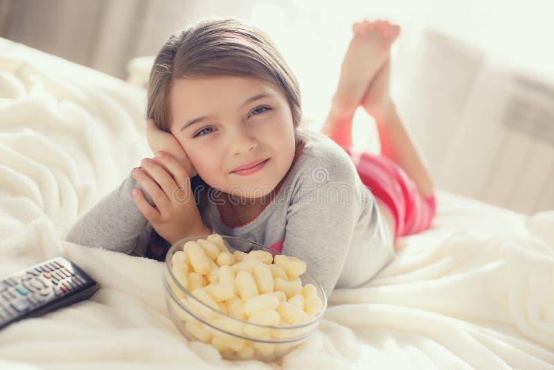 Meisje die popcorn in bed eten stock afbeeldingen