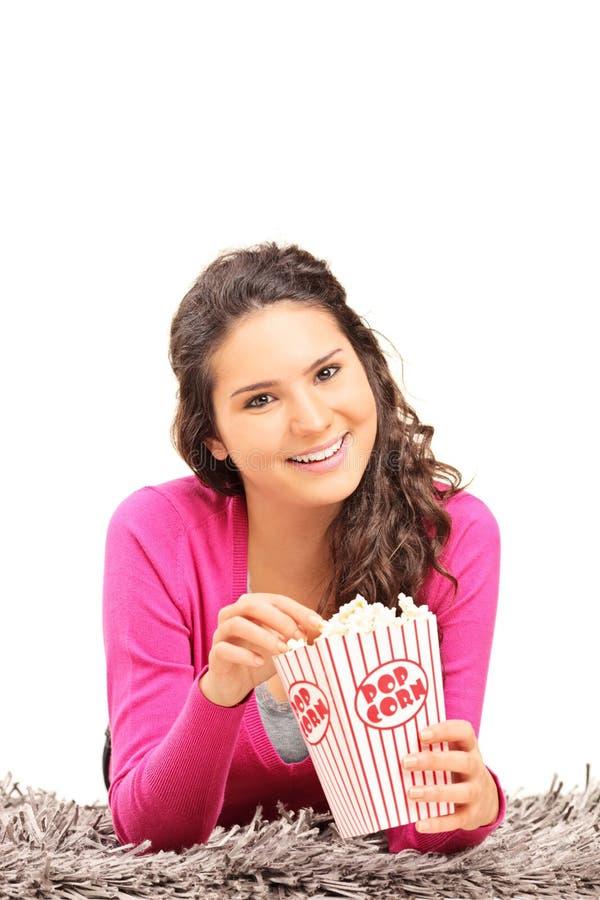 Meisje die popcorn eten en op een tapijt liggen royalty-vrije stock afbeelding