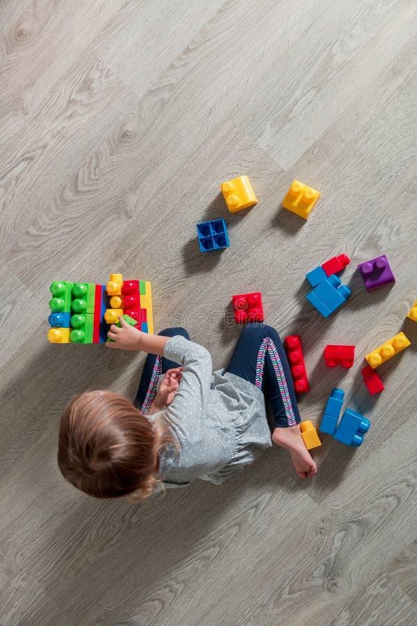 meisje die pret en bouwstijl van heldere plastic bouwblokken hebben royalty-vrije stock foto