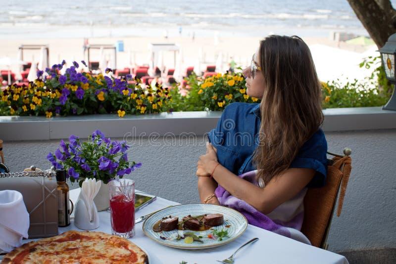 Meisje die in restaurant op het strand eten royalty-vrije stock afbeeldingen