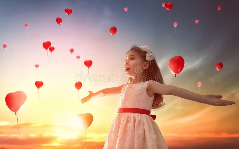 Meisje die rode ballons bekijken stock afbeeldingen