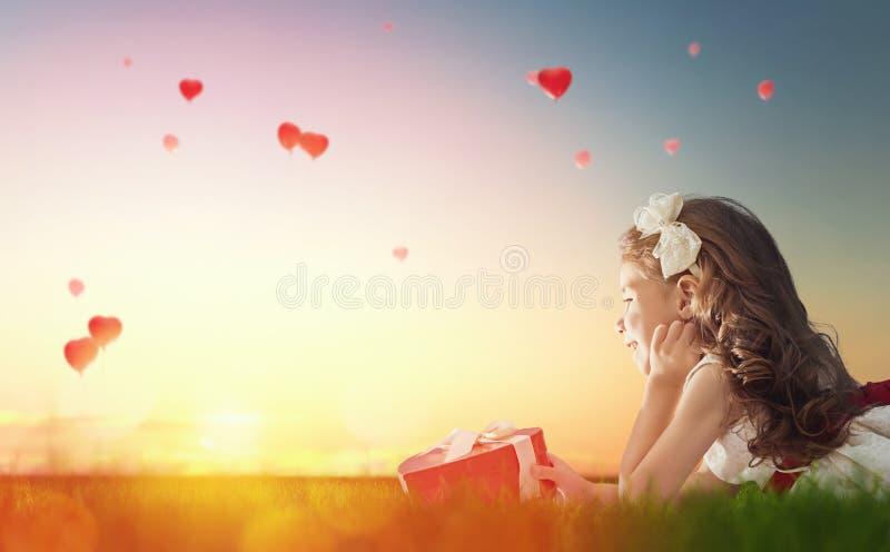 Meisje die rode ballons bekijken stock foto