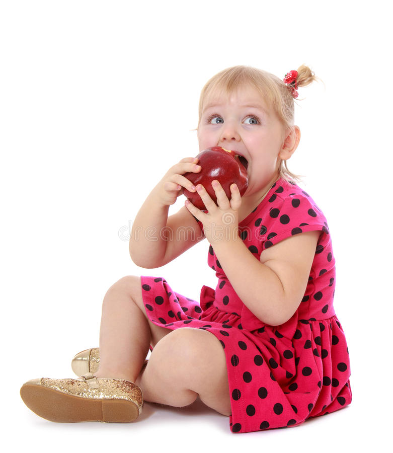 Meisje die in rode kleding een appelzitting eten royalty-vrije stock foto's