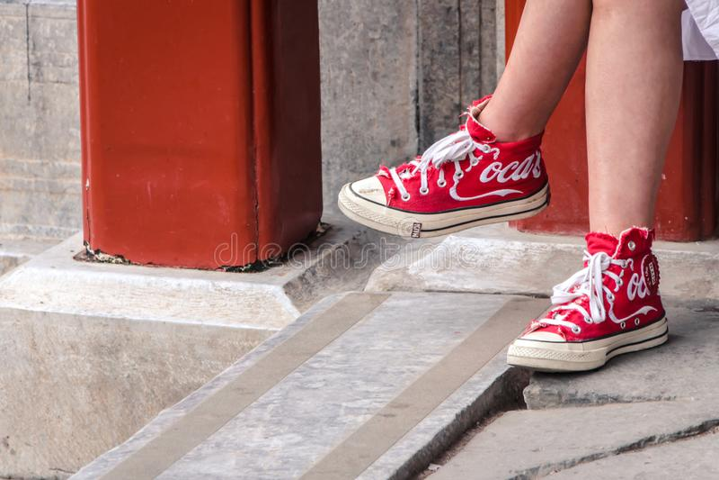 Meisje die Rode Schoenen met Coca Cola Logo op het dragen stock foto's