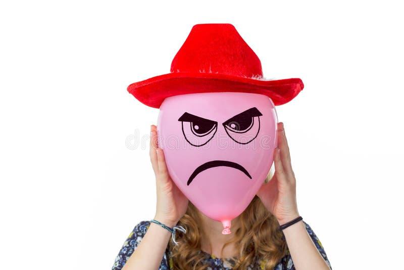 Meisje die roze ballon met boos gezicht en rode hoed houden stock foto's