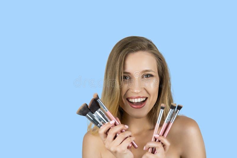 Meisje die roze borstels houden die geïsoleerde blauwe achtergrond glimlachen royalty-vrije stock afbeeldingen