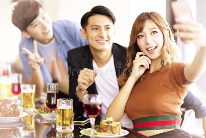 meisje die selfie met haar vrienden bij het diner maken royalty-vrije stock fotografie
