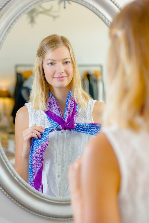 Meisje die sjaal vooraan spiegel proberen royalty-vrije stock fotografie