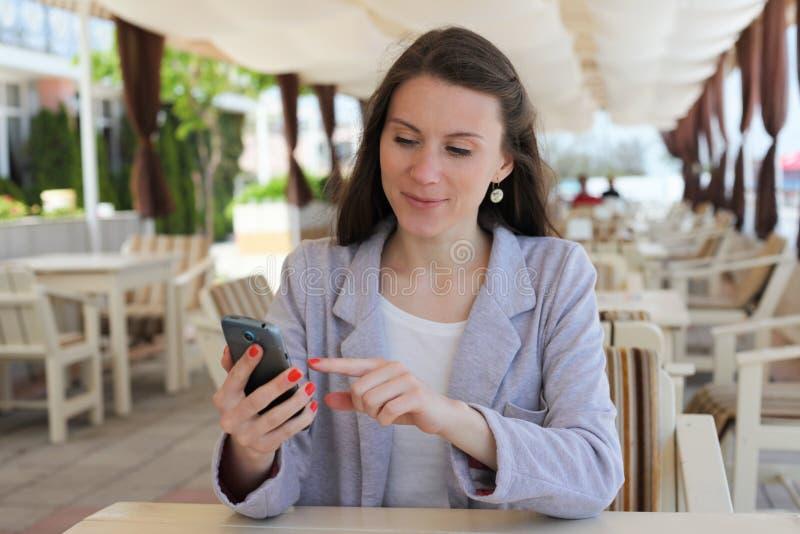 Meisje die slimme telefoon in een restaurantterras met behulp van stock afbeeldingen