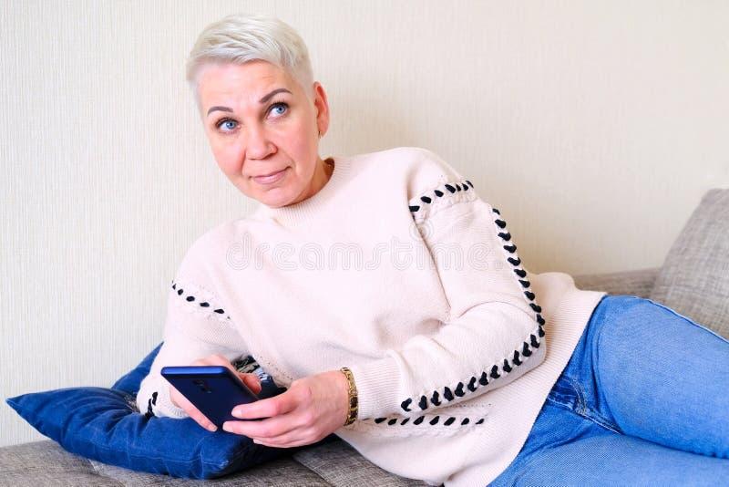 Meisje die SMS in smartphone lezen De emotie van blije verrassing Het korte kapsel van vrouwen Modieus modieus profiel met stock foto