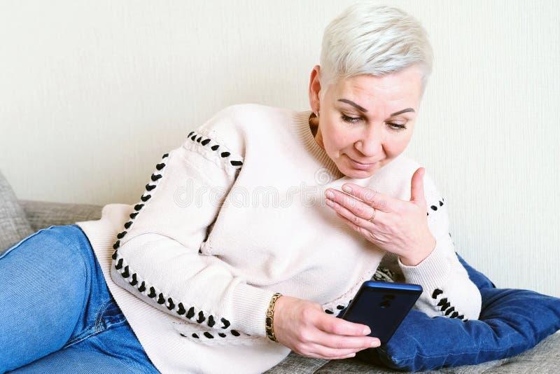 Meisje die SMS in smartphone lezen De emotie van blije verrassing Het korte kapsel van vrouwen Modieus modieus profiel met stock afbeeldingen